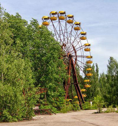 Une grande roue ouillée à Tchernobyl entourée d'arbres