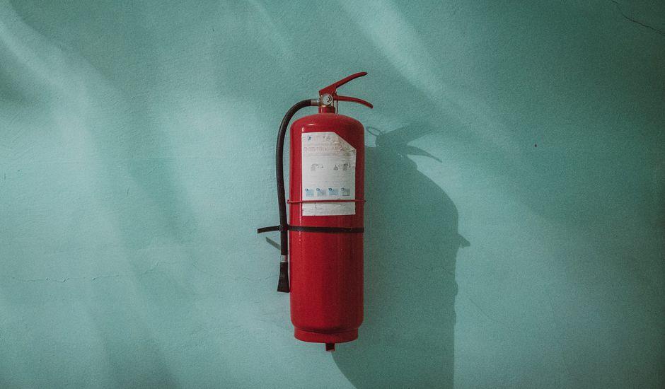 Un extincteur rouge accroché à un mur.