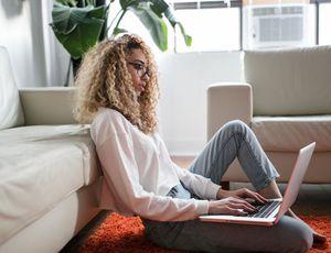 une jeune femme sur son ordinateur travaillant de chez elle