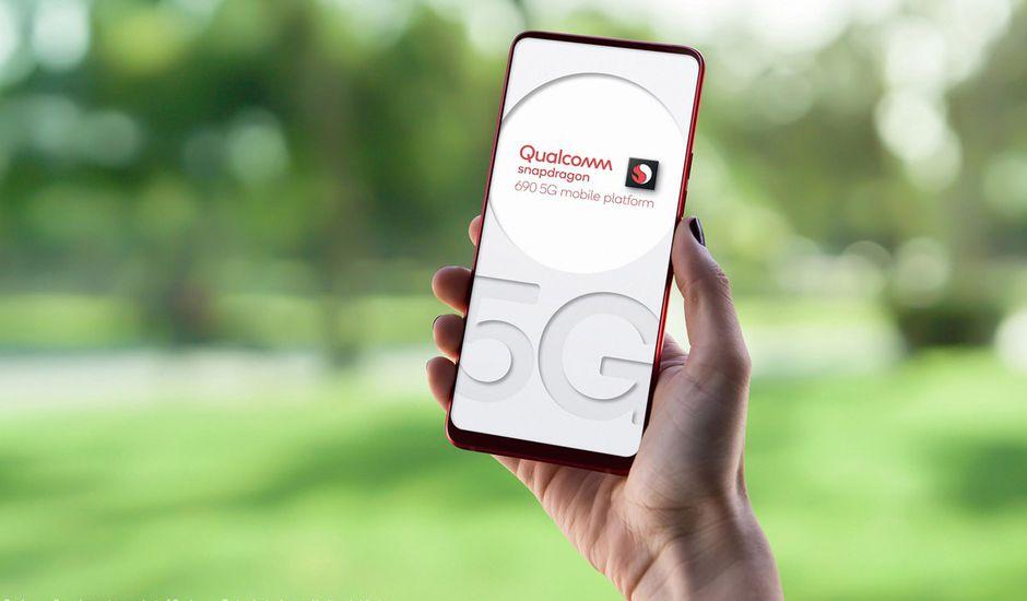 Un homme tient un smartphone dans les mains qui affiche un visuel présentant le processeur Snapdragon 690 de Qualcomm.