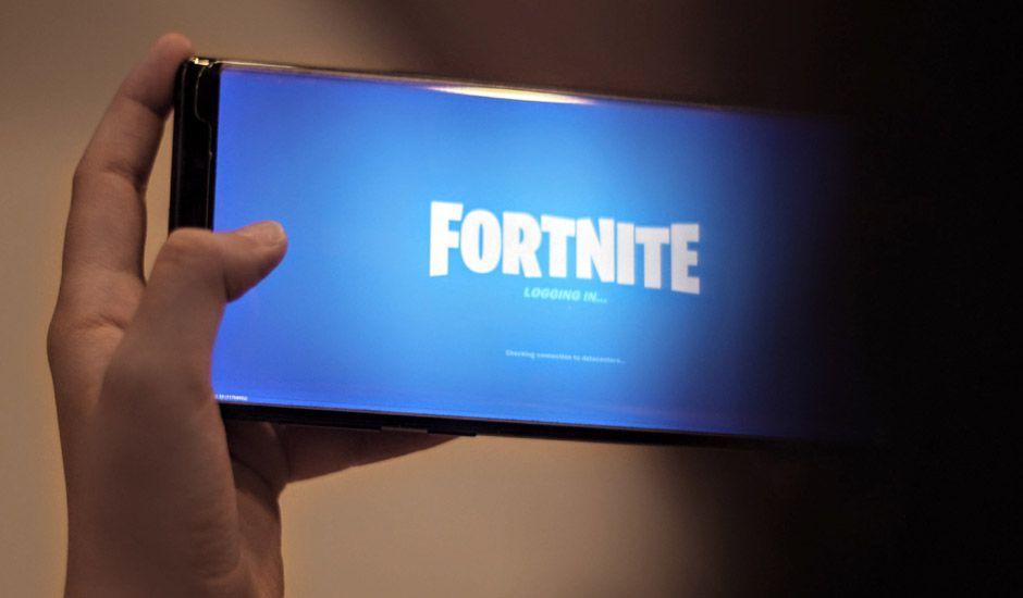 Une personne tenant un smartphone avec Fortnite.
