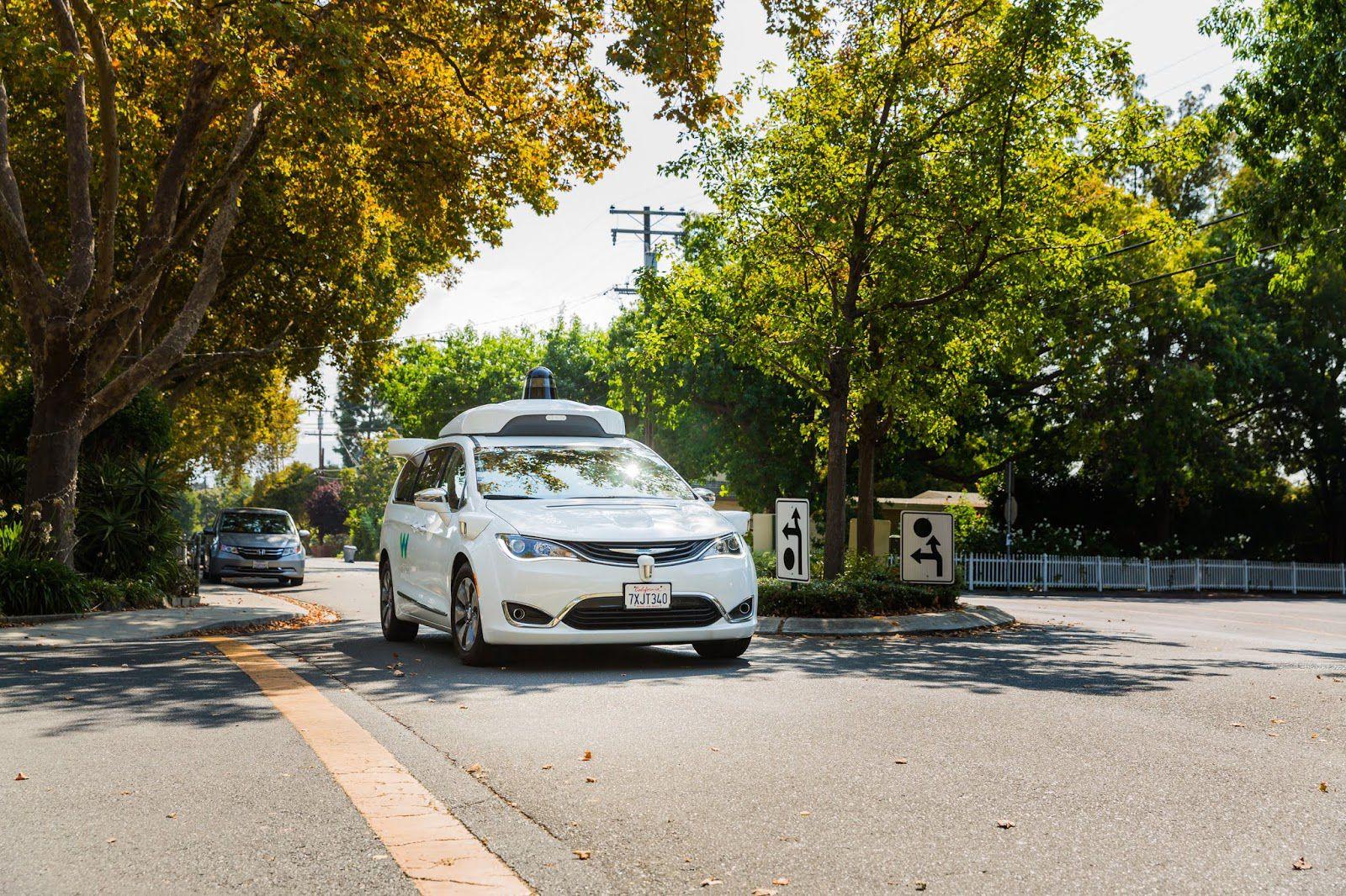 Une voiture de Waymo avance sur une route entourée d'arbres.