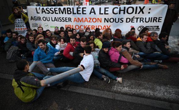 """Photographie qui montre une trentaine de militants contre la politique d'Amazon pendant une action de désobéissance civile. Ils sont assis par terre, agrippés entre eux, avec une banderole """"Agir ou laisser Amazon nous détruire""""."""