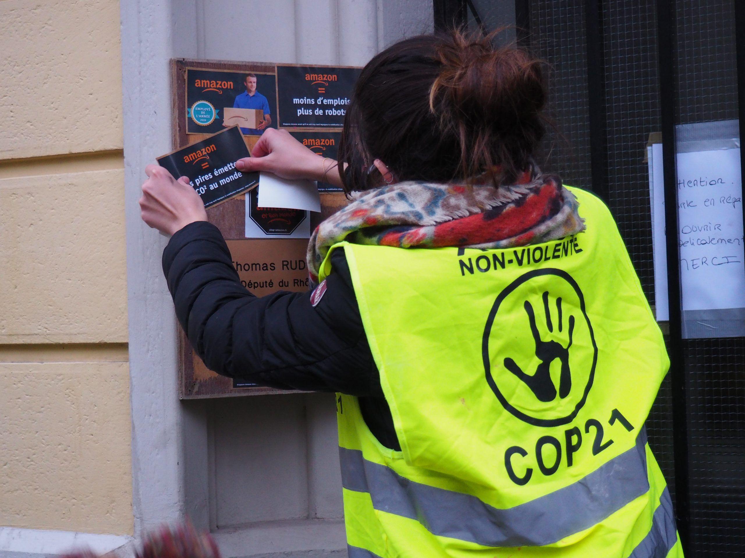 Sur la photo une militante colle un stickers sur la plaque de permanence du député Thomas Rudigoz