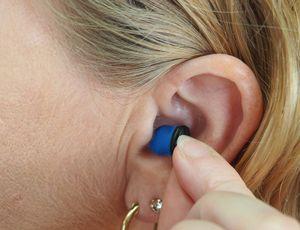 Une femme place un écouteur intra-auriculaire dans son oreille.