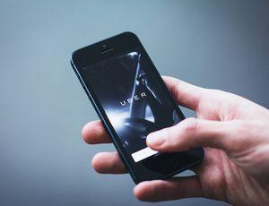 Une main tenant un smartphone ouvert sur l'application Uber.