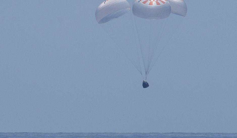 La capsule Crew Dragon avec ses quatre parachutes déployés sur le point de se poser sur la mer