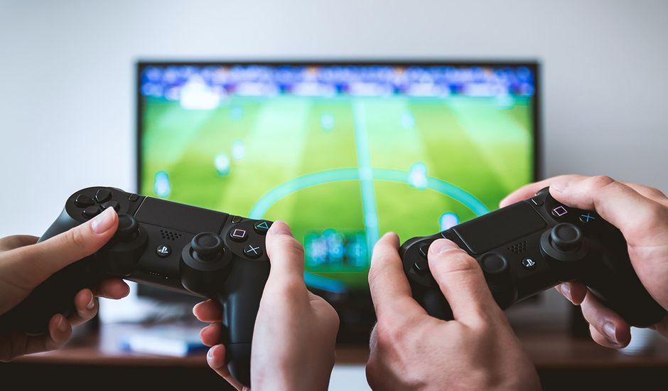 Deux joueurs tiennent des manettes de PS4 devant un écran de télévision.