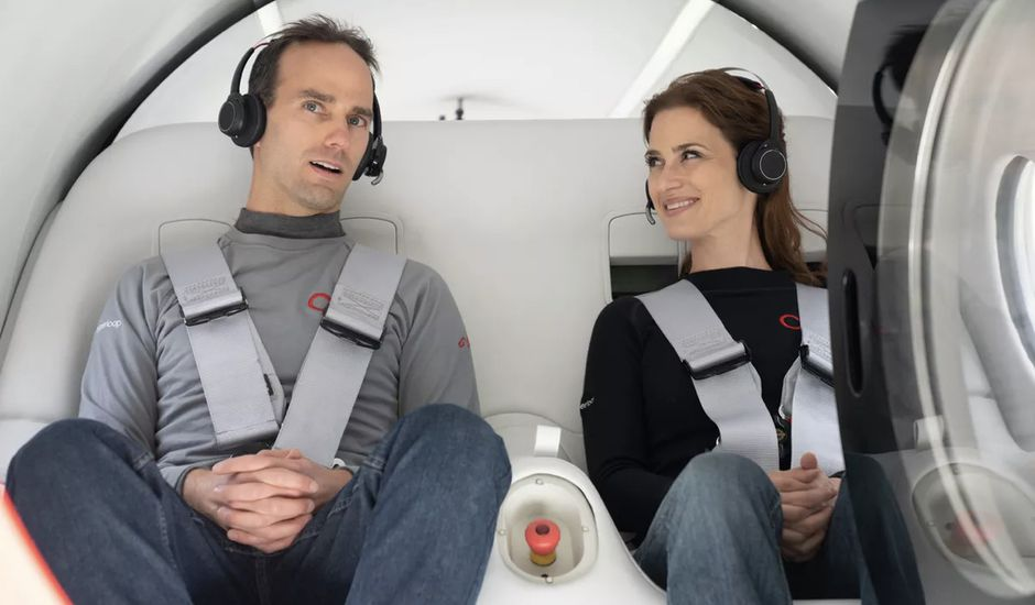 Un homme et une femme assis dans une capsule de Virgin Hyperloop.