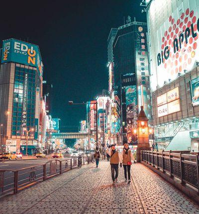 Un couple marche dans les rues illuminées d'une ville japonaise.