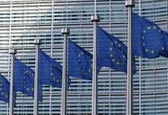 Plusieurs drapeaux de l'Union Européenne flottent devant un building.