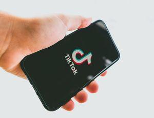 Un homme tient un smartphone avec TikTok dans les mains.