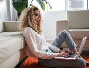 une jeune femme avec son laptop sur la moquette