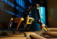 Le robot Spot tient un tuyau avec son bras robotique.