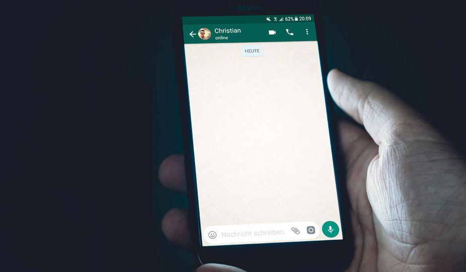 Une main tenant un smartphone avec une discussion WhatsApp ouverte.