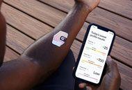 Un homme lit les informations sur son smartphone livrées par le patch qui est collé sur son avant-bras.