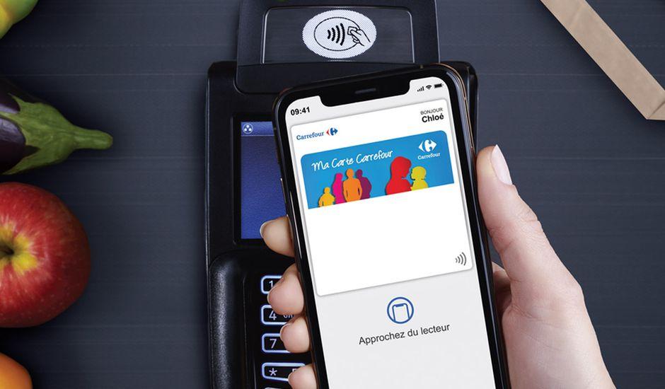 Un téléphone mobile avec la carte de fidélité Carrefour dans Apple Pay effectue un paiement sans contact sur un TPE.