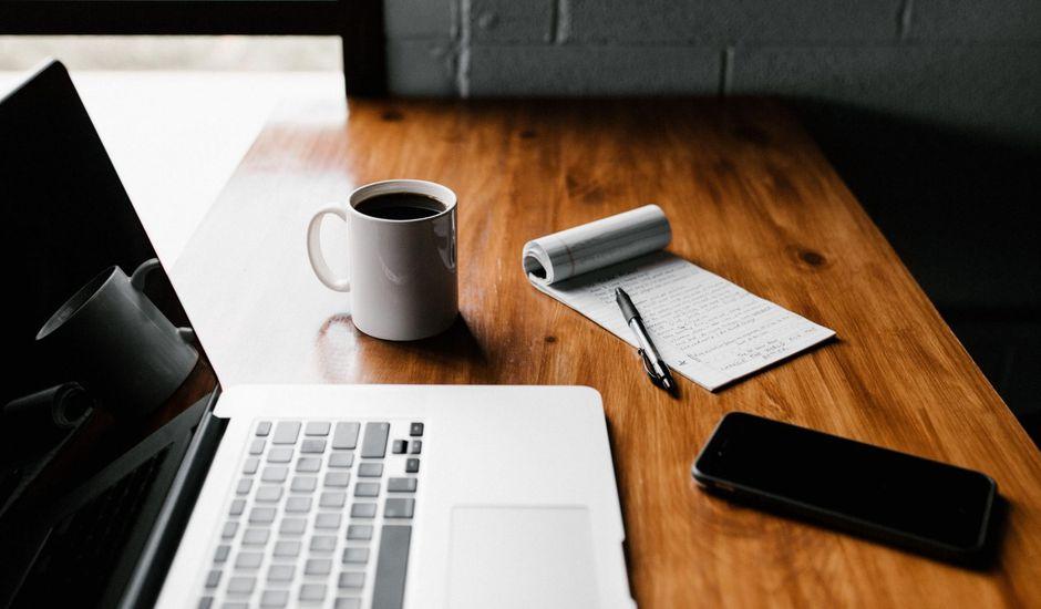 un bureau avec ordinateur et bloc note