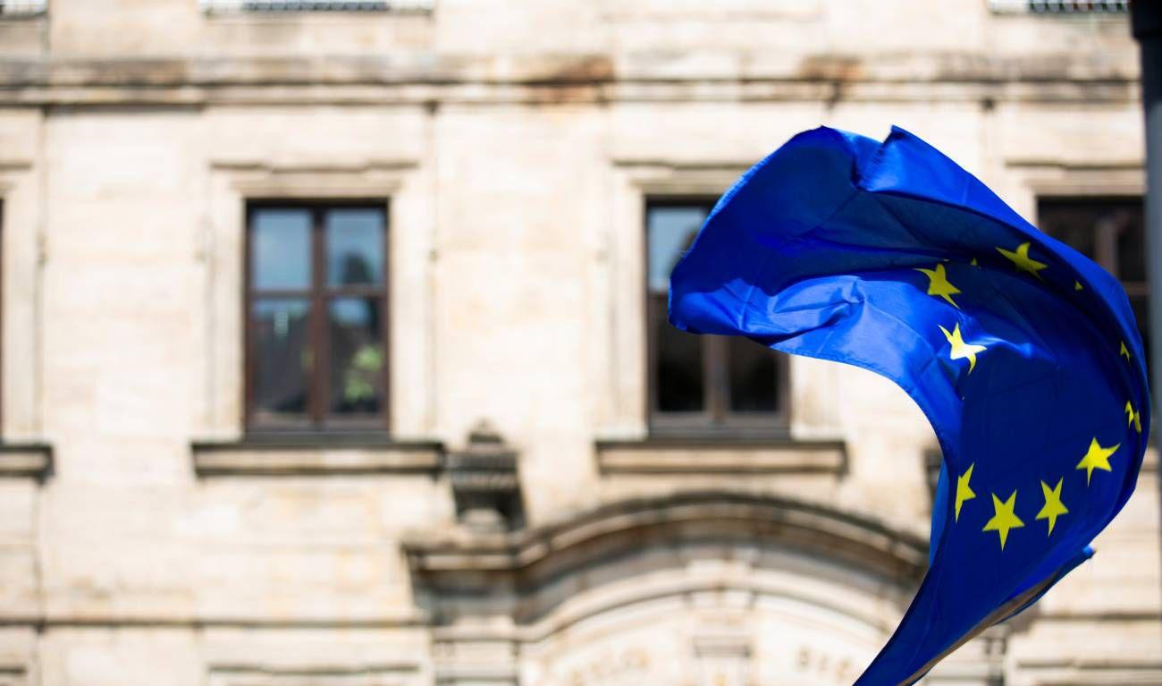 Le drapeau de l'Union européenne flotte devant un bâtiment.