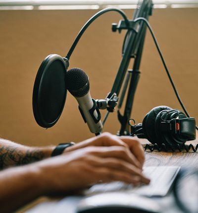 enregistrer un podcast - Photo de mains proches d'un clavier et d'un micro