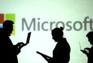 Logo de Microsoft avec des personnes regardant leurs ordinateurs