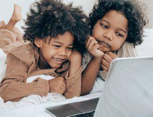 Deux enfants regardent un écran d'ordinateur portable.