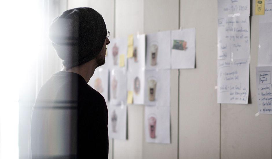 une personne regardant des éléments affichés sur un mur