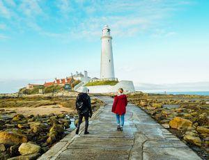 Deux personnes marchant sur une digue qui rejoint un phare
