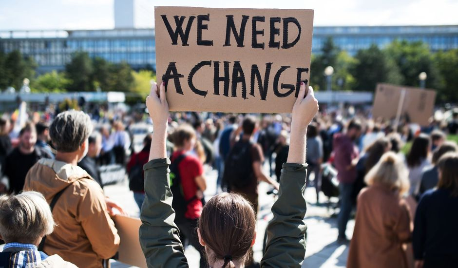"Une manifestante tenant un paneau ""We need a change"""