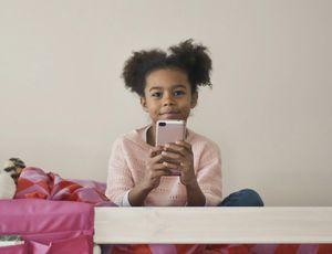 Une petite fille tient un smartphone dans ses mains.