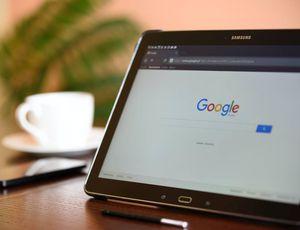 Une tablette affiche la page d'accueil du moteur de recherches Google.