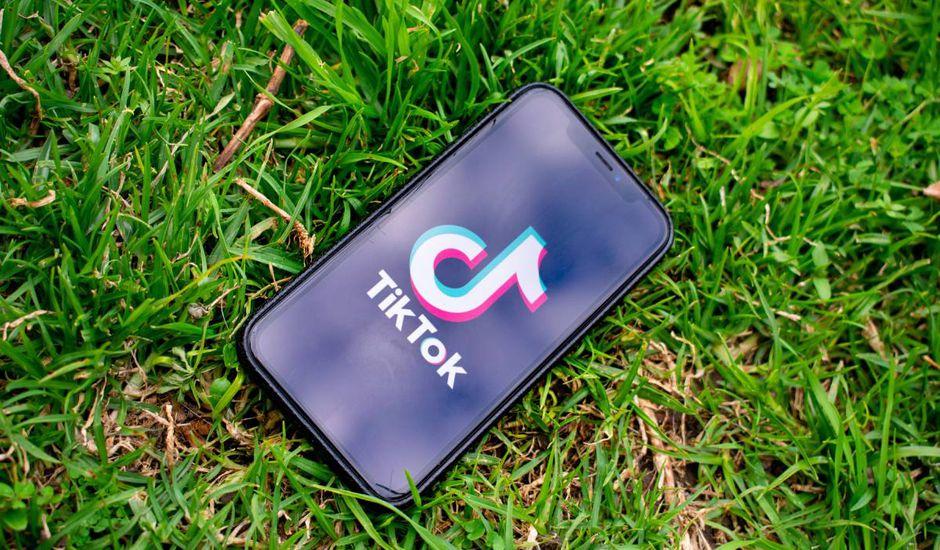 Un smartphone posé sur du gazon sur lequel apparaît le logo de TikTok.