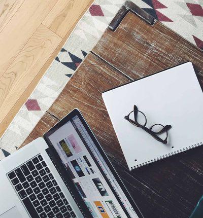 Image illustrant un ordinateur et une feuille où sont posées des lunettes, le tout sur un bureau