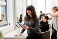 une femme consultant une tablette dans un salon de coiffure