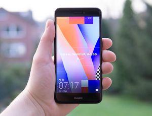 Une personne tient un smartphone Huawei dans la main.