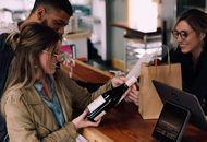 Un coupe achète une bouteille de vin dans un commerce de proximité.