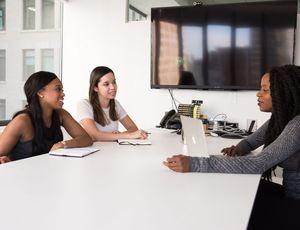 3 femmes échangeants en salle de réunion