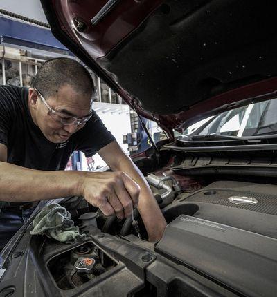 Un garagiste répare le moteur d'une voiture.