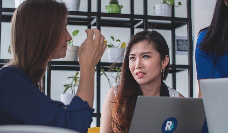 deux femmes discutant au bureau