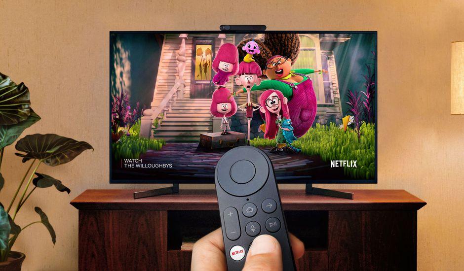 Un homme tient une télécommande et regarde un écran branché sur Portal TV.