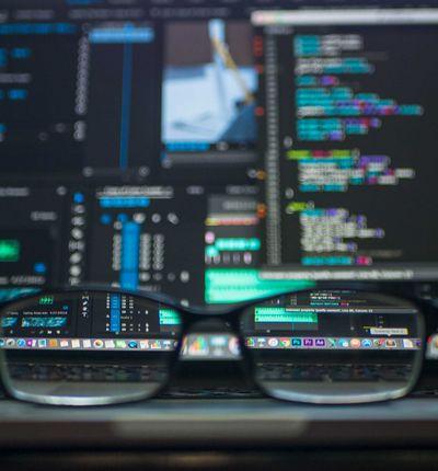 Des lunettes de vue posées devant un écran affichant du code informatique