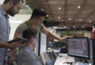 trois employés regardant des lignes de code