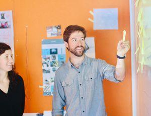 deux collaborateurs discutant devant un tableau