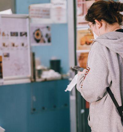 une femme avec un masque consulte son smartphone