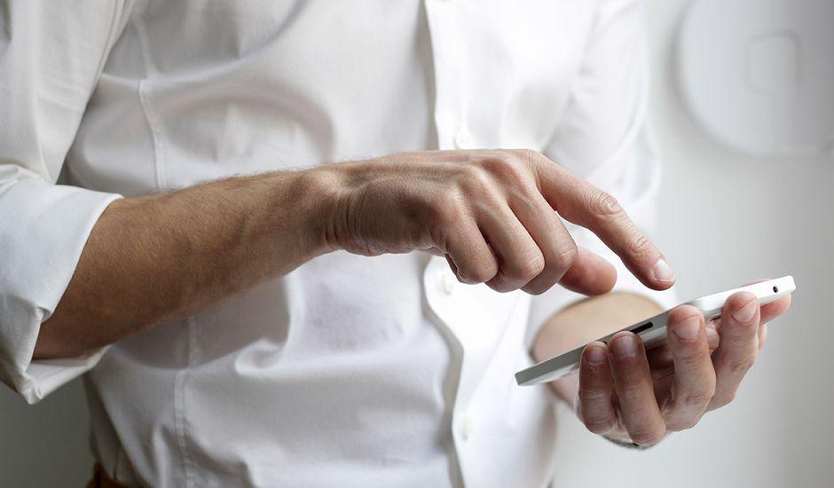 Publicité digitale : un homme sur son smartphone sur le point de cliquer