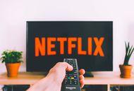 Netflix le logo sur une TV avec une personne qui tient sa télécommande