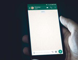 Un homme tient un téléphone affichant une conversation WhatsApp.