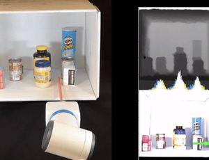 Un bras robotique range des objets dans une étagère.