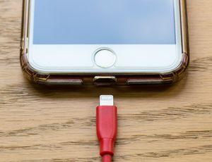 Un iPhone 6 et son chargeur sont posés sur une table.