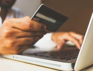 Un homme tient sa carte bleue pour faire des achats sur son ordinateur.